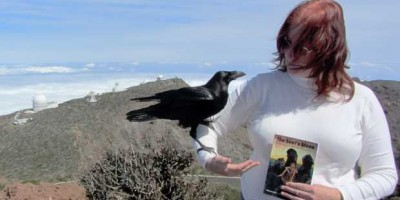 Sheila holding Carmelo the raven and her book 'The Seer's Stone' at the Roque de Los Muchachos