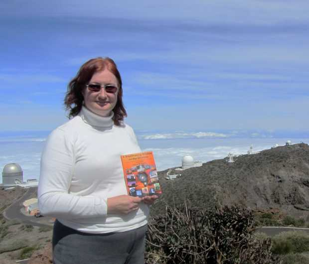 Sheila Crosby holding 'A Breathtaking Window on the Universe' with the telescopes of the Roque de Los Muchachos behind
