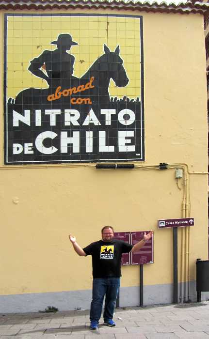 Tim Johnson, in front of the old Chillean nitrate sign in Santa Cruz de La Palma, wearing a T shirt with the same sign