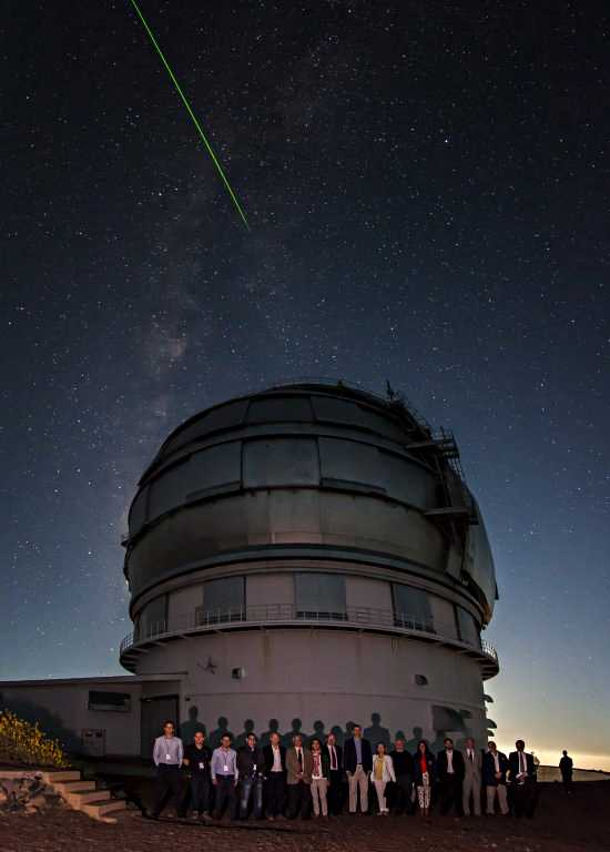 His Majesty the King, authorities, and personnel of the IAC and the GTC beside the building which houses this telescope,at the Roque de los Muchachos Observatory (La Palma). Above the telescope is a laser beam emitted from the William Herschel Telescope. Credits: Antonio González/IAC.
