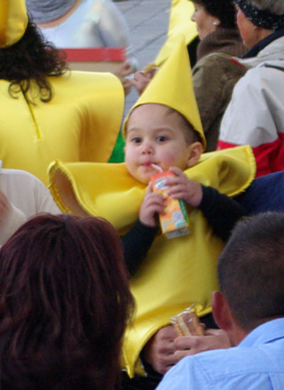 A baby in a star costume, drinking juice