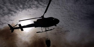 Backlit helicopter with a bag of water. in Mazo. Photo: Saul Santos