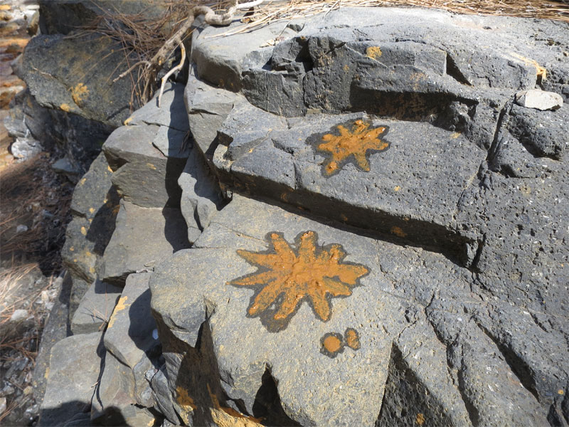 Yellow stars painted with ochre on the rocks beside the Limonero. Caldera de Taburiente, La Palma