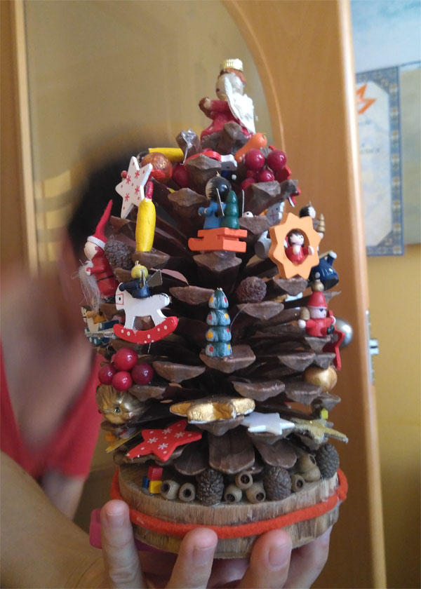 A Christmas 'tree' made from a big pine cone decorated with tiny wooden candles and figures