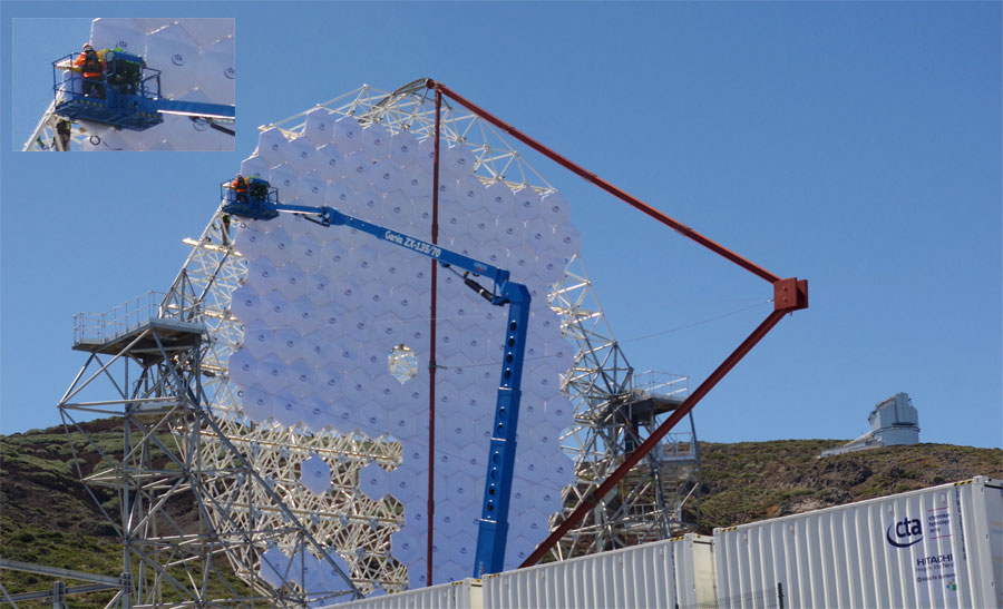 The massive segmented mirror of the Large Size Telescope and two people in a cherry picker working on the mirror